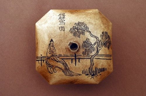 An appealing pipe-bowl adorned with the portrait of a woman sitting under a willow tree.  From: The Art of Opium Antiques
