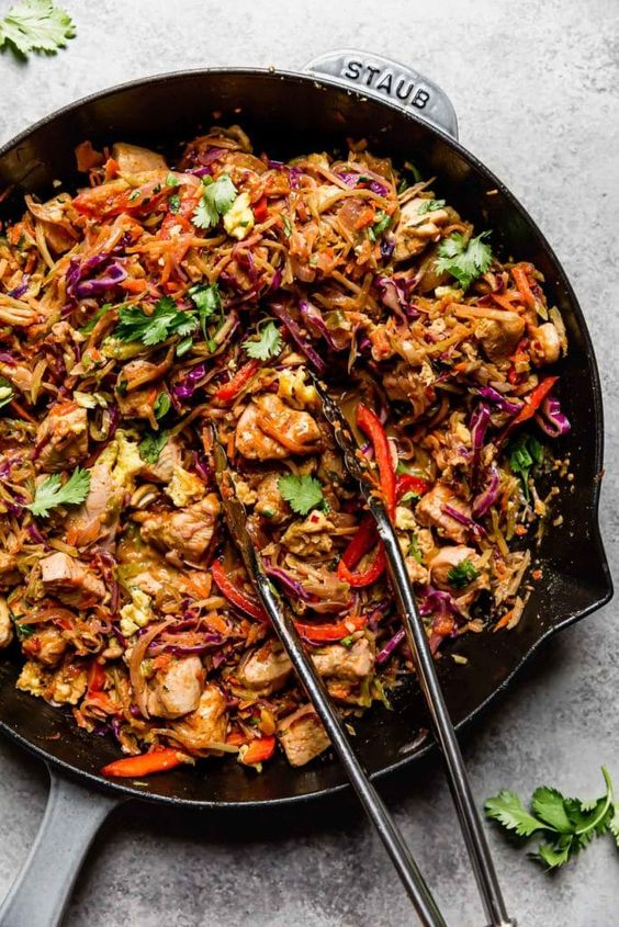 Loaded with veggies and full of flavor this one-skillet Healthy Chicken Pad Thai recipe makes for a healthy, easy, and delicious weeknight meal! Strands of broccoli slaw, cabbage, and carrots stand-in for noodles making this healthy Pad Thai a satisfying Whole30, paleo, and gluten-free meal. You won't even miss the noodles!