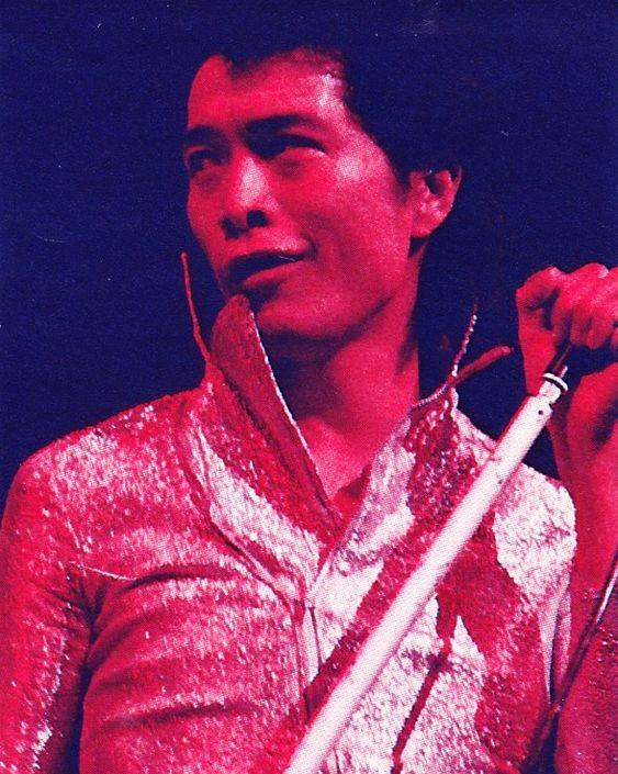 マーブル模様のシャツを着てスタンドマイクを握っている矢沢永吉の画像
