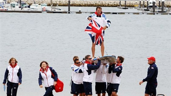 Nick Dempsey of Great Britain is carried onshore on his windsurf board by Team GB team mates after winning the silver medal in the RS:X Men's Sailing on Day 11 of the London 2012 Olympic Games at the Weymouth & Portland venue