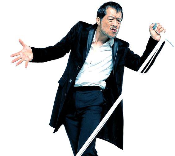 スタンドマイクを握ってポーズをきめている矢沢永吉の画像