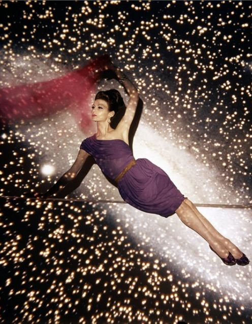 A model becomes the center of the universe in this conceptual photograph by John Rawlings. With the galaxy as a backdrop, she appears to float in the middle of the Milky Way by leaning on a subtle edge. She wears a violet evening dress by Maurice Rentner with one pleated shoulder strap that drapes to the waist. The stunning work appeared in the July 1, 1960, Vogue, near the end of Rawlings's 30-year career with Condé Nast.