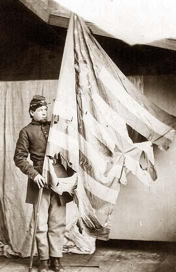 photograph of a battle worn Old Glory from the Civil War, circa 1864, soldier is from the 37th Pennsylvania Infantry