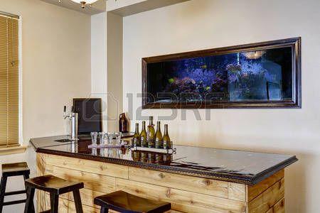 parete bar: Morbido avorio bar sala con costruito in acquario a muro. Armadio in legno con lucido bancone top nero