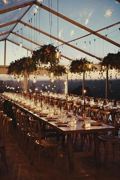 Warm lighting and draped foliage set the mood for ethereal elegance. Coupled with a translucent tent that mirrors the night sky, this space is like a midsummer night's dream. #RusticCountryWeddingStyle