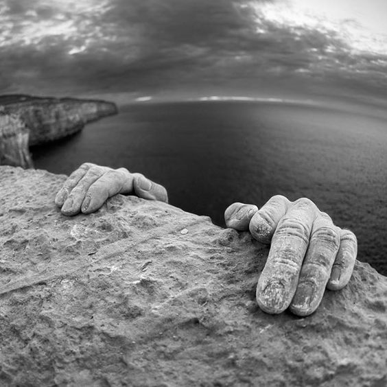 It's a detail of Tommy Caldwell's hands topping out after climbing a sea cliff on the island of Malta. Corey Rich Productions