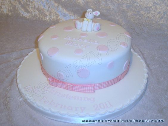 Round christening cake elegantly decorated and a simple pink polka dot decoration and ping iced christening message and name. Finished with a pink gingham ribbon and topped with a clay rabbit