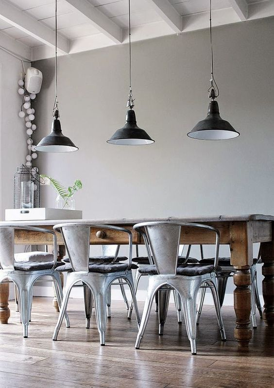 low hanging statement lights, centred tabled with curved back tuck in chairs. Grey walls Wooden floor: