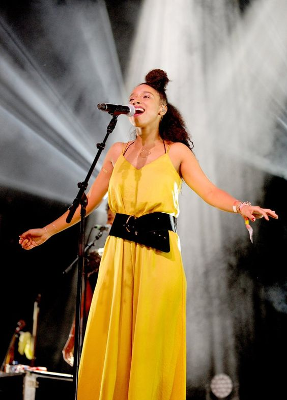 Pin for Later: Lianne La Havas's Style Is Unstoppably Cool  Looking angelic on stage at Glastonbury, Lianne sang to fans in a yellow slip cinched in at the waist with an oversize patent belt.