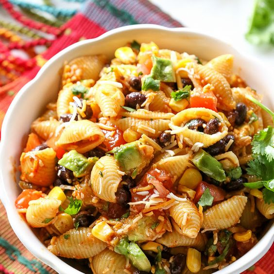 Taco Pasta Salad Recipe Salads with pasta shells, black beans, corn, cilantro, tomatoes, salsa, olive oil, lime juice, taco seasoning, garlic, salt, pepper, Mexican cheese blend, avocado
