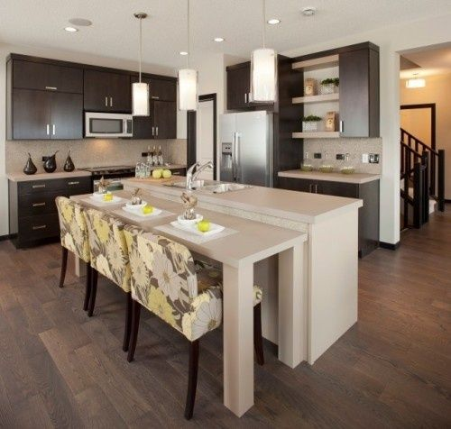 Comfortable seating for all ages with table height rather than bar height island in this modern kitchen with a beautiful mix of dark stain and light paint finishes