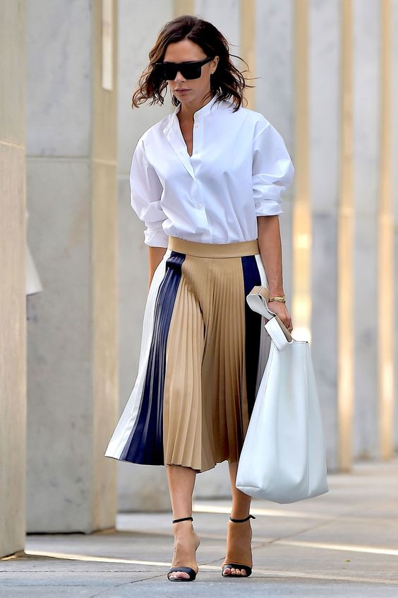 Victoria Beckham indossa una camicia bianca senza colletto con una gonna in plissè e sandali con cinturino