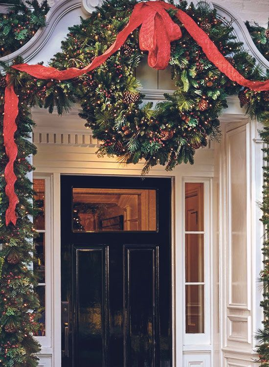 Christmas front door with black painted door, huge wreath and red ribbon