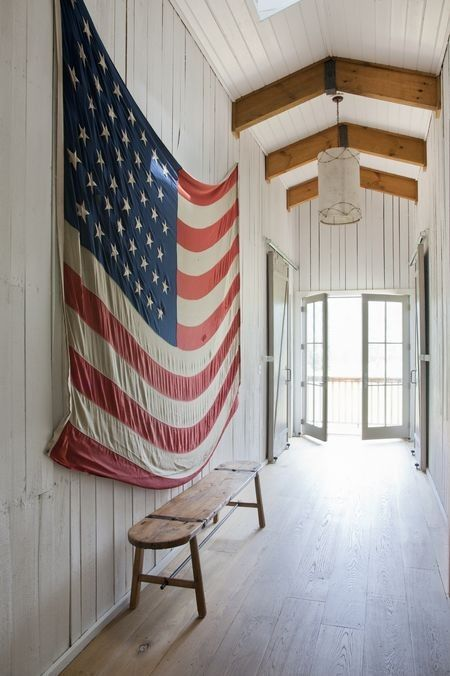 American flag hung on the wood paneled wall of a barn interior with beautiful country charm, a rustic bench, and skylight. #americana #americanflag #patriotic #farmhousestyle #barn #countryliving #4thofjuly #memorialday #redwhiteblue
