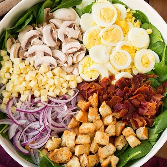 """""""Spinach Salad with Warm Bacon Dressing Yield: About 5 servings Ingredients · 12 oz bacon, cooked (drippings and browned bits from pan reserved), crumbled, divided · 5 large eggs, boiled, peeled and sliced · 9 oz baby spinach · 6 oz button mushrooms, sliced · 1/2 small red onion, thinly sliced (run under cool water to remove harsh bite) · 1 cup shredded or finely cubed swiss cheese · 2 1/2 cups homemade or store bought croutons (optional) · 3 Tbsp reserved bacon drippings with browned bits ·…"""