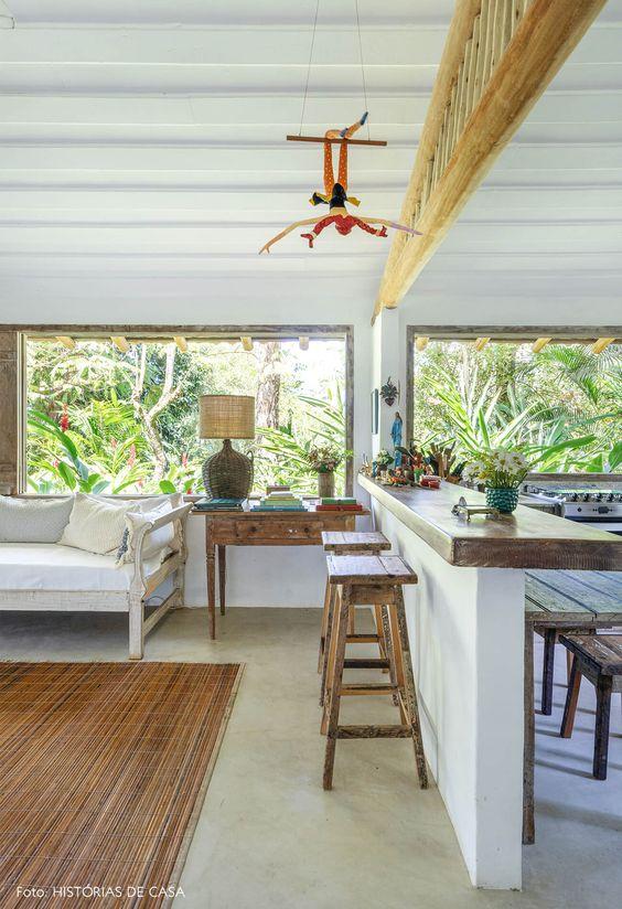 Sala de estar de casa na praia em meio à floresta tem esquadrias de madeira, sofás brancos com almofadas, aparador de madeira rústica e bancada para integração com a cozinha.