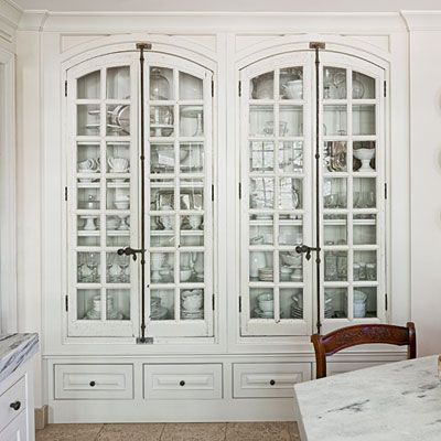 Built-ins make beautiful solutions for any space and ensure that there is a place for everything. This dreamy china cabinet features antique French windows as doors, plenty of space for china, and a base outfitted with Pacific Silvercloth for storing silver.