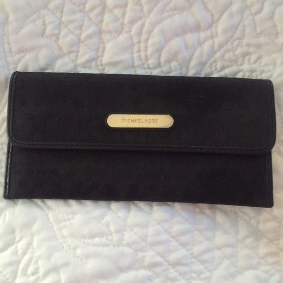 Michael Kors Wallet Used black Michael Kors Wallet. This wallet snaps shut with buttons, had 4 slots for cards, a section for cash, and a change zipper on the back. This wallet is used, but it great shape! Only warn marks are pictures (scratches on the gold Michael Kors plate on the front) Michael Kors Bags Wallets