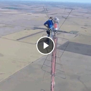 Homem em um lugar muito alto instalando um satélite.