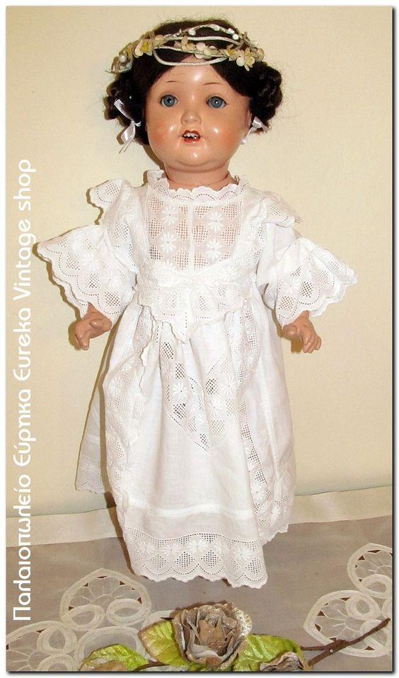 Κούκλα νύμφη ντυμένη φτιαγμένη από την πιο διάσημη Γερμανική εταιρία Armand Marseille. Η εταιρία αυτή κατασκεύαζε κούκλες την περίοδο 1885 έως το 1930. Το σώμα της είναι φτιαγμένο από παπιέ μασέ, το κεφάλι από ένα είδος πορσελάνης που στα αγγλικά αναφέρεται με το όνομα bisque. Τα μαλλιά της δεν είναι αληθινά, τα μάτια είναι γυάλινα και ανοιγοκλείνουν. Το φόρεμα είναι χειροποίητο.  Σε γενικές γραμμές είναι σε πολύ καλή κατάσταση για την ηλικία της. Έχει ύψος 52εκ.