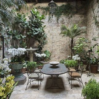A secret garden courtyard with walls of stone. Romantic French Country Garden Courtyard Ideas. #frenchcountry #courtyard #dining #garden