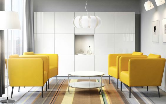 A modern conference room with yellow armchairs, a white round coffee table and storage with white doors