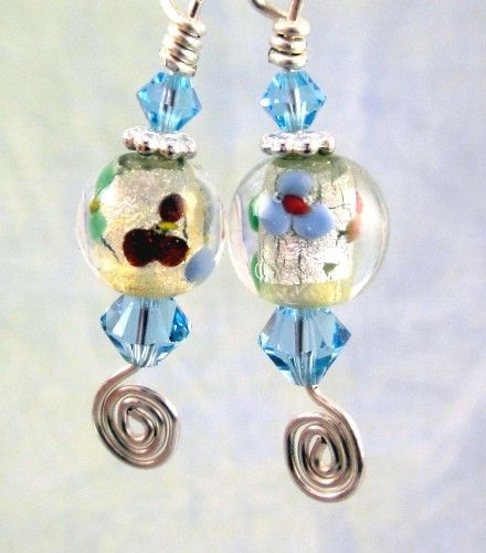 Dichroic lampwork glass orbs centered between light blue Swarovski crystals with silver accent earrings.  These earrings dangle and shimmer with the clear orbs with silver foil under tones and red and