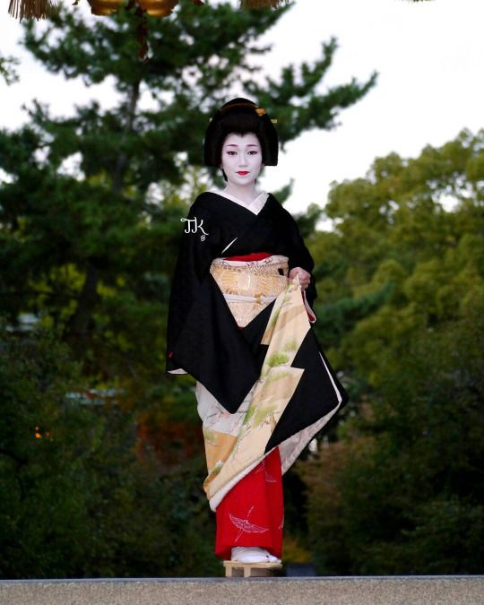Geiko Ichimomo wearing a formal black kimono, possibly on the day of her erikae