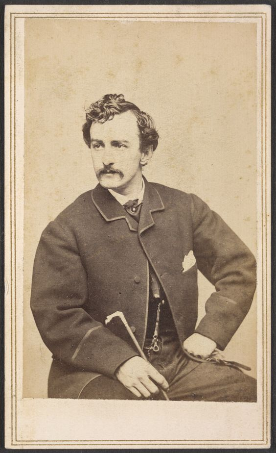 [John Wilkes Booth seated, with cane in hand]