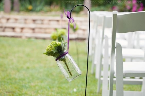 mason jars with flowers hanging from shepherds hook