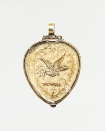 Pendant in the form of a crowned heart, front view: 18th century - Pendant in the form of a crowned heart, front view. Gold background and double-sided with faceted rock crystal covers in hinged gold collets enclosing two panels of silk embroidered with pictures in hair. Its front shows a dove bearing a sprig of forget-me-not. The reverse shows a landscape with a couple walking towards a house. Both scenes are traditional symbols of wooing and marriage.