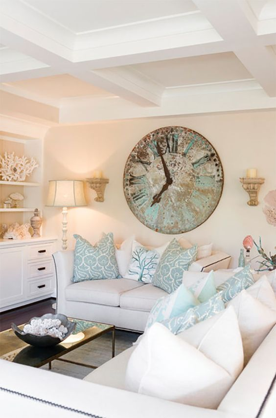 Enjoy the feeling of being at a coastal retreat all the time by decorating your living room with beachy accents like pillows, coral sculptures and light, airy shades.: