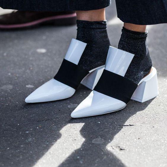 Chunky-heel mules. White patent leather with thick black elastic strap. Heather grey socks. -MB