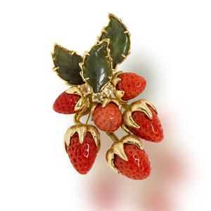 A coral, nephrite jade and yellow sapphire brooch, Tony Duquette  designed as a six coral strawberries with nephrite jade leaf surmount and oval-shaped yellow sapphire detail; signed Tony Duquette; estimated total sapphire weight: 2.00 carats; mounted in eighteen karat gold; length: 2 1/2in.: