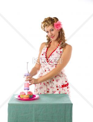 smiling young woman decorating cupcakes portrait of a beautiful young woman smiling while decorating