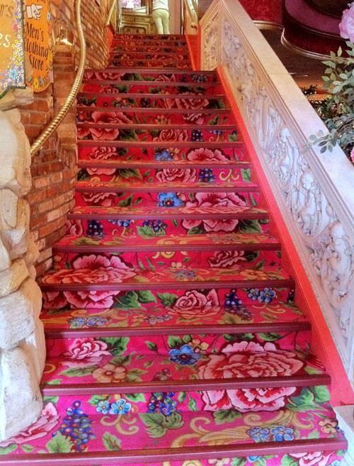 Le tapis d'escalier ne fait pas dans la discrétion ! Ici les marches et contremarches s'habillent d'un textile rose vif très couture avec ses grands motifs de fleurs fuchsia.