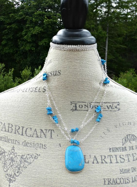 Necklace has center pendant in silver metal frame combined with silver chain and blue Turquoise stone chips. Necklace is lightweight longest point is 24 inches. Silver lobster clasp. Pendant in center