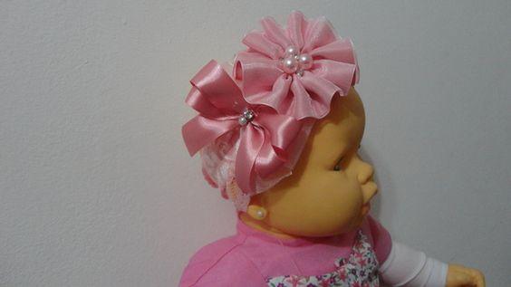 Faixa em renda com elastano larga na cor rosa com laço de fita de cetim e de organza, rosa e flor de fita de cetim e organza com miolo de pérolas e strass. R$ 22,95