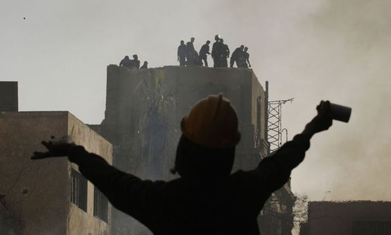 An Egyptian protester gestures towards riot police during a demonstration in Cairo's Tahrir Square on January 26, 2013. (Mohammed Abed/AFP)