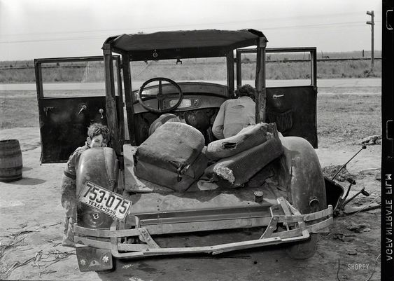 """February 1939. """"White migrant and wife repairing clutch in their car near Harlingen, Texas."""""""