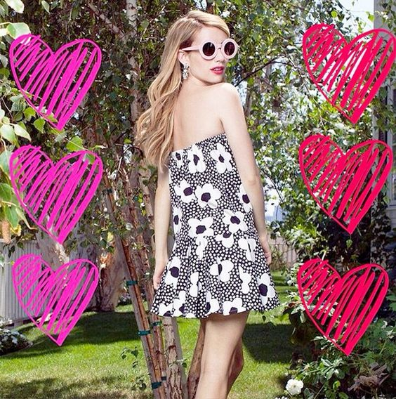 Emma Roberts in a printed strapless dress and pink sunnies