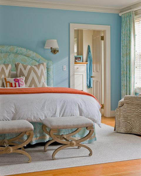 source: Honey Collins    Sky blue walls paint color, blue silk headboard, taupe ikat chevron pillows, orange throw, ottomans and faux bois fabric chair.