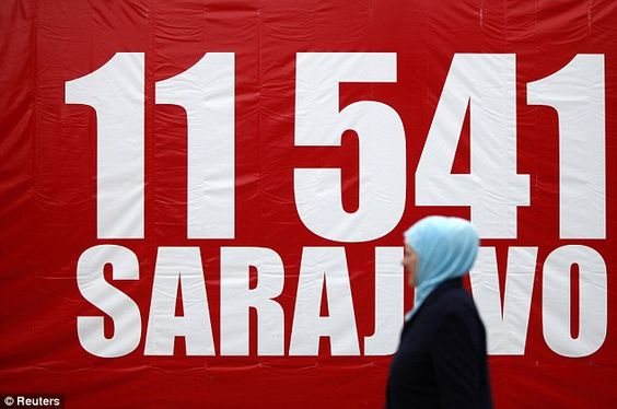 Remembered: A Bosnian Muslim woman walks near a banner with the number 11,541, to symbolise red chairs, along Titova street in Sarajevo as the city marks the 20th anniversary of the start of the Bosnian war