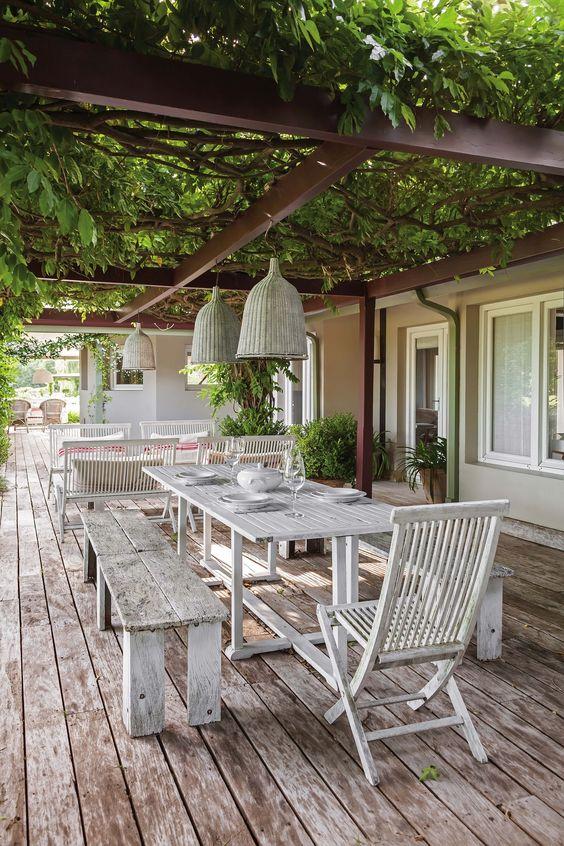 Deck con mesas de madera y sillones blancos con gran pérgola verde que une la…