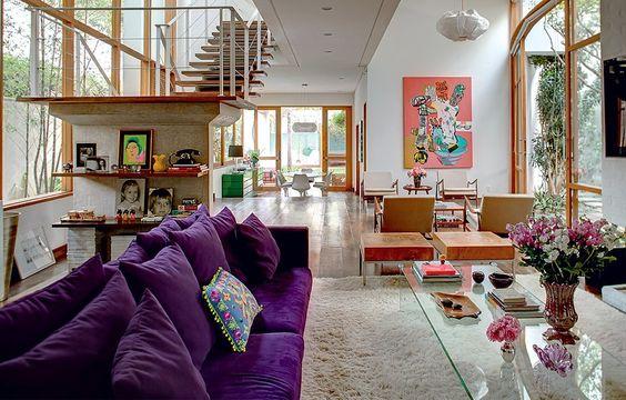 Na sala ampla e clara, o confortável sofá púrpura reina absoluto. Objetos em tons de rosa predominam nos detalhes: