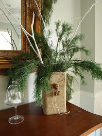 Branches that have been spray painted white and some greenery in a vase covered with burlap