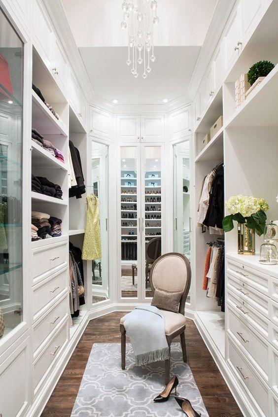 white walk in closet with a chair as a center piece #white #closet #storage #organization #allenrothCloset #allenAndRothCloset #closetShelves