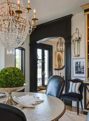 Black and white dining room with dramatic empire style chandelier and round dining table. Beautiful Classically Refined Rooms on Hello Lovely Studio.