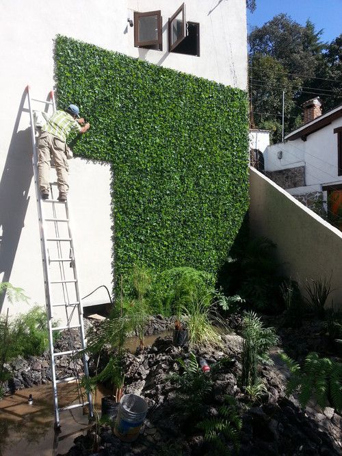 The latest project. Artificial leaf panels give this stark white wall a vertical garden feel without the maintenance and upkeep of regular hedge panels.: