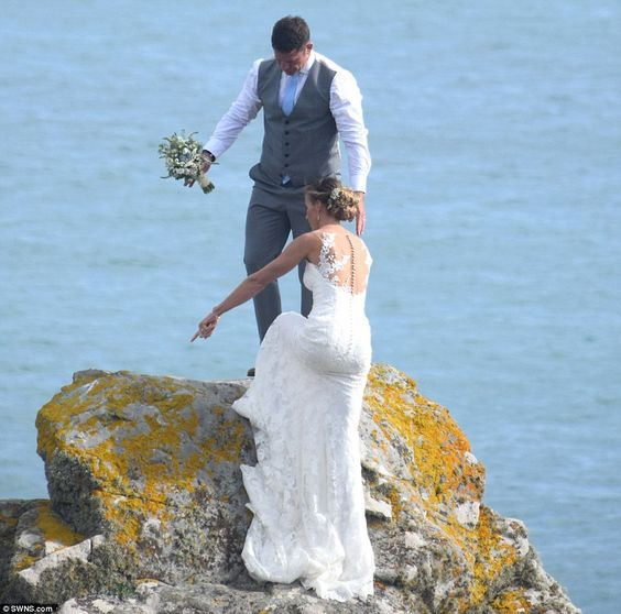 Up you come: Presenter Steve gallantly helped his new bride as they climbed onto the mossy outcrop: